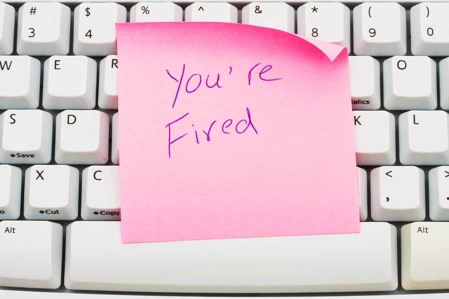 A pink sticky note sitting on a computer keyboard You are fired
